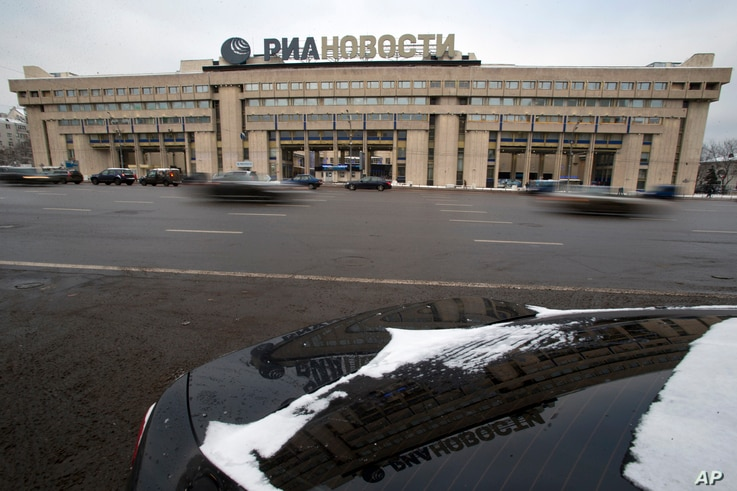 FILE - Cars pass by the former Russian RIA Novosti information agency headquarters in Moscow, Dec. 9, 2013.  Major brands in the export division of Russian media include RT, the RIA Novosti news agency, Sputnik and the Voice of Russia radio station.