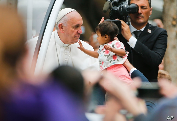 An unidentified child, carried from the crowd, touches Pope Francis' face as he heads to celebrate Sunday Mass on the Benjamin Franklin Parkway in Philadelphia, Sept. 27, 2015.