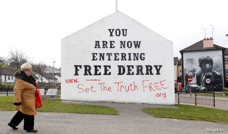 A woman walks past murals in Bogside, Derry, Northern Ireland, March 23, 2010. The Bloody Sunday massacre took place in Derry in 1972.