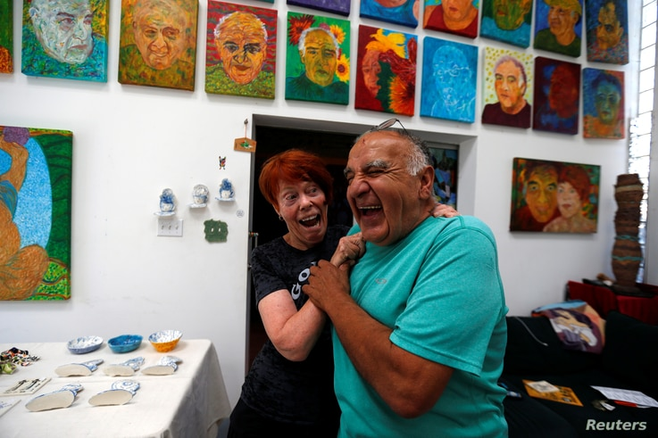 Artists Gonzalo Duran and his wife Cheri Pann laugh in the studio of their Mosaic Tile House in Venice, California, Aug. 26, 2016.
