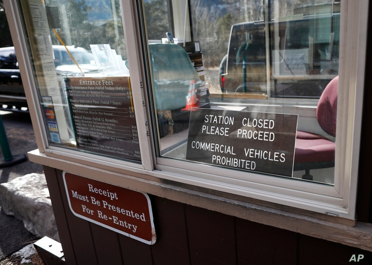"""Vehicles pass by freely in the background as a fee booth sits unmanned at the east entrance to Rocky Mountain National Park, in Estes Park, Colo., Jan. 20, 2018. National parks are to remain as """"accessible as possible"""" during a government shutdown th..."""