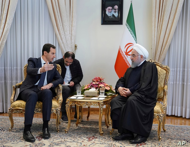 In this photo released by the Syrian official news agency SANA, Syrian President Bashar al-Assad, left, speaks with Iranian President Hassan Rouhani during their meeting in Tehran, Syria, Feb. 25, 2019.