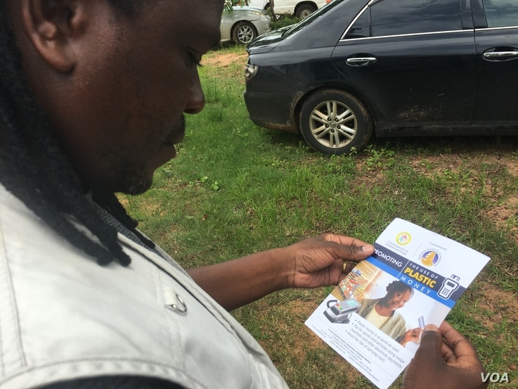 A man reading a Reserve Bank of Zimbabwe flyer promoting the use of plastic money to ease the country's over-a-year problem of cash shortages, Gokwe, Zimbabwe, Jan. 31, 2017. (S. Mhofu/VOA)