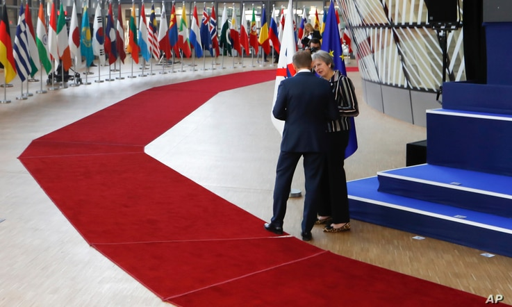 British Prime Minister Theresa May, right, speaks with European Council President Donald Tusk after a group photo at an EU-ASEM summit in Brussels, Oct. 19, 2018.