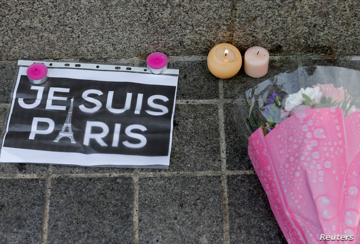"""Candles, flowers and a leaflet with the slogan """"I am Paris"""" are left in tribute to victims of Paris attacks in central Strasbourg, France, Nov. 14, 2015."""