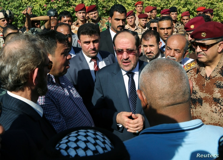 Iraq's Prime Minister Nouri al-Maliki, center, attends the funeral ceremony of Major General Negm Abdullah Ali, commander of the army's sixth division, at the defence ministry in Baghdad, July 7, 2014.