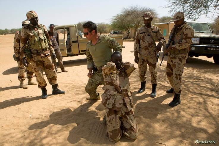 FILE - A U.S. special forces soldier demonstrates how to detain a suspect during Flintlock 2014, a U.S.-led international training mission for African militaries, in Diffa, Niger, March 4, 2014.