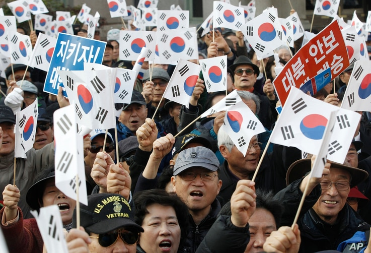 Protesters supporting South Korean President Park Geun-hye wave national flags during a rally opposing her resignation in Seoul, South Korea, Nov. 17, 2016.