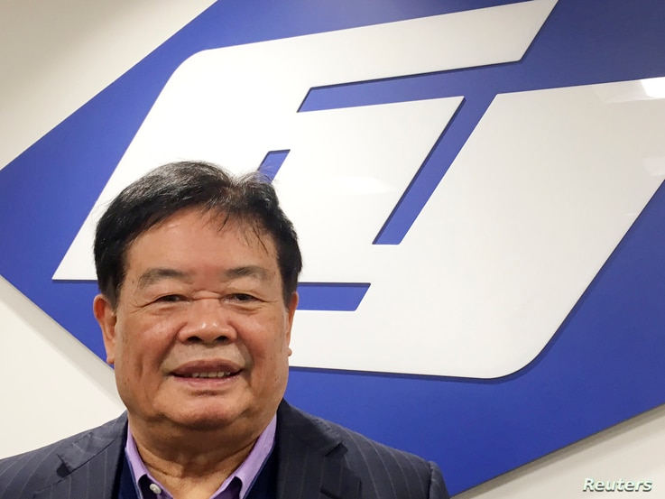Cao Dewang, chairman of Fuyao Glass, a Chinese-based leading supplier of automotive glass worldwide, poses in front of the corporate logo at the primary Fuyao Glass production plant in the United States, in Moraine, Ohio, Sept. 30, 2016.