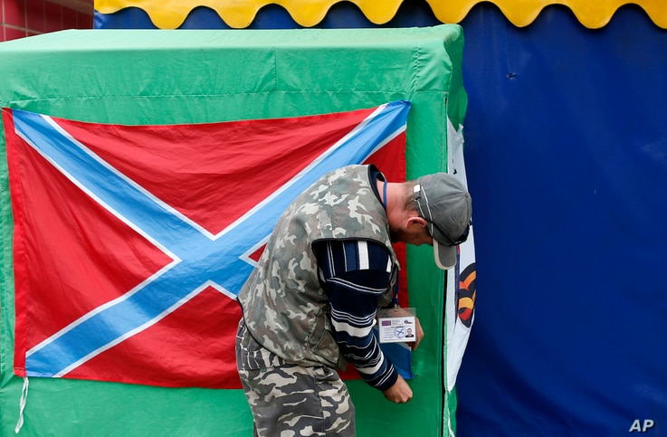 A Pro-Russian rebel arranges a flag of the self-proclaimed Federal State of Novorossiya in the town of Donetsk, eastern Ukraine, Tuesday, Sept. 16, 2014. The city council in Donetsk says three people have been killed and five wounded in shelling over...
