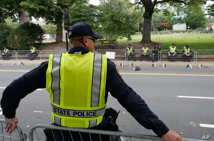 State Police patrol the road in front of Market Street park with the statue of Confederate General Robert E. Lee as they lock down the downtown area in anticipation of the anniversary of last year's Unite the Right rally in Charlottesville, Va., Aug....
