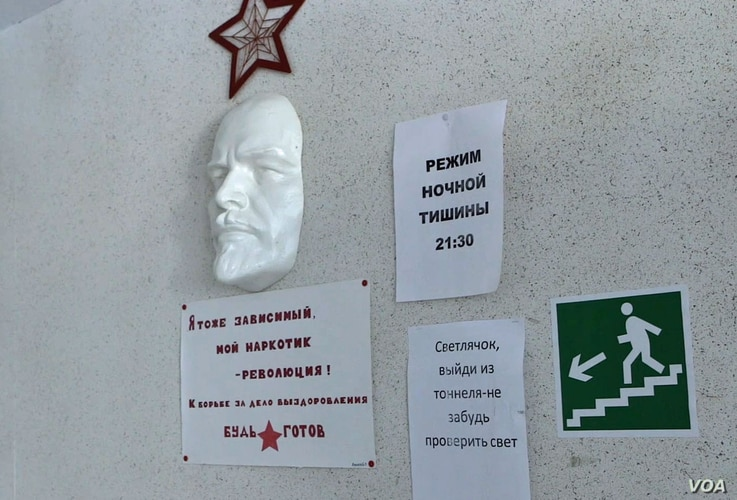 """A face mask of Russian communist revolutionary Vladimir Lenin is seen at the Vershina-Navigator Foundation's rehabilitation center. The sign beneath reads """"I'm also addicted. Revolution is my narcotic!"""""""