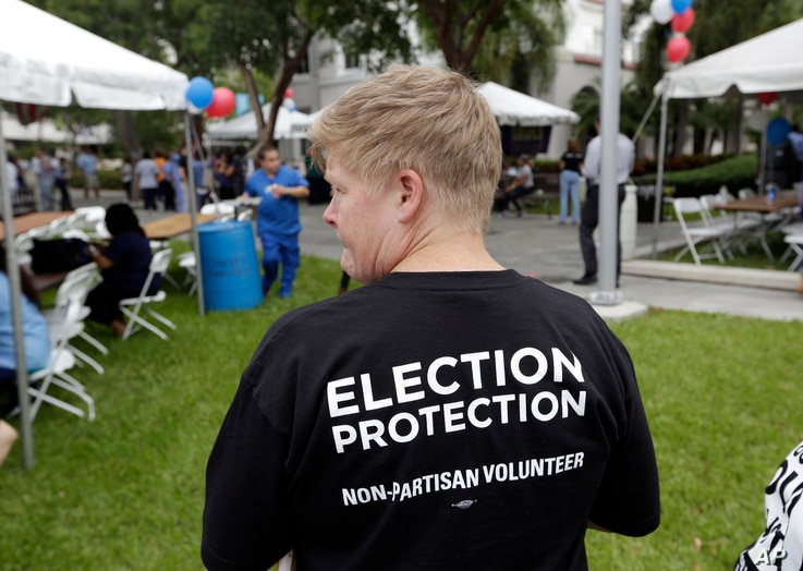 Lisa Hubbard, a volunteer with the non-partisan Election Protection Coalition, attends an early voting celebration outside of Jackson Memorial Hospital, on the first day of early voting in Miami-Dade County for the general election, Oct. 24, 2016, in...