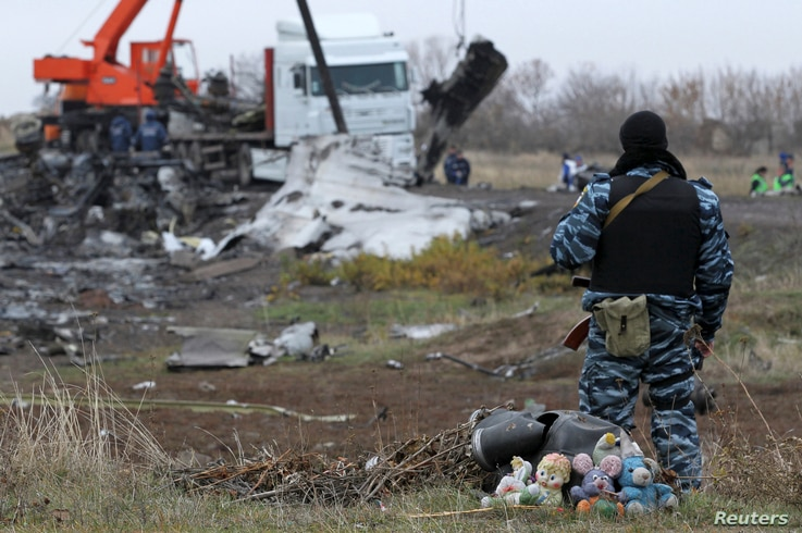 A pro-Russian armed man secures crash site wreckage of the Malaysia Airlines Flight MH17 at the site of the plane crash near the settlement of Grabovo in the Donetsk region, Nov. 16, 2014.