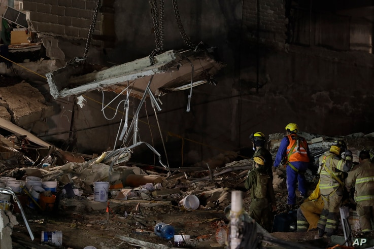 Rescue workers use a crane to lift a section of concrete floor as they remove rubble in hopes of reaching dozens of people believed to be trapped inside a collapsed office building since a 7.1 magnitude earthquake, in the Roma Norte neighborhood of M...