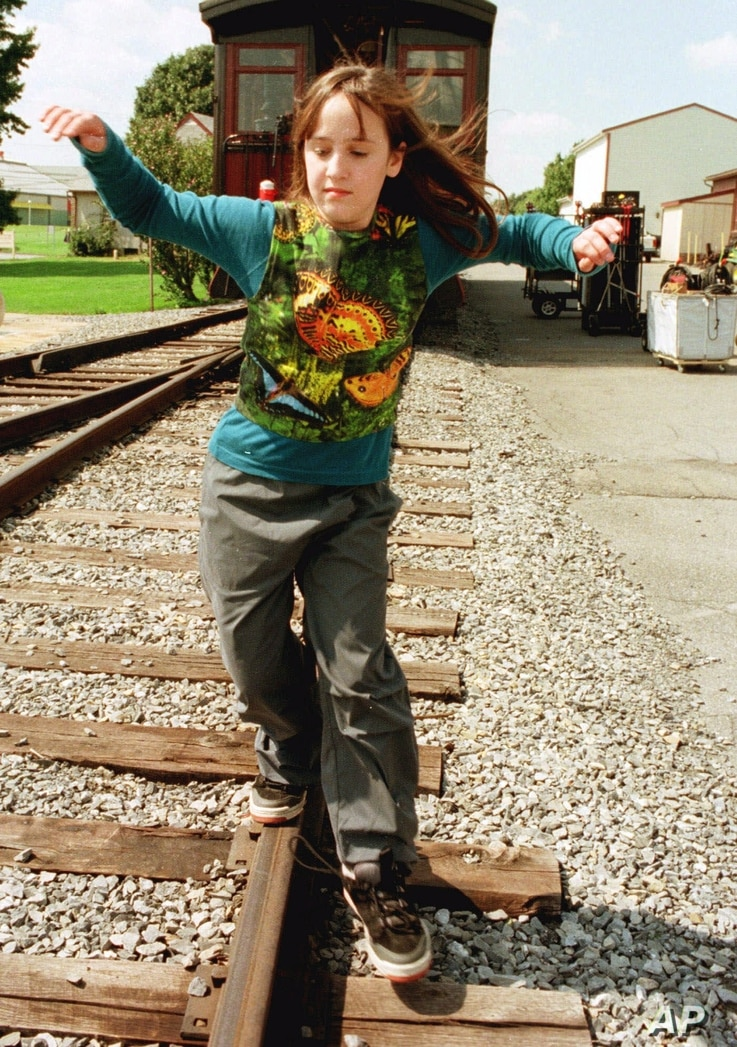 """Actress Mara Wilson balances herself as she walks the rails as she relaxes during a lunck break in the filming of """"Thomas and the Magic Railroad"""" in Strasburg, Pa., Sept. 13, 1999."""