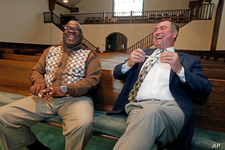 Bishop Clarence Green of Hopewell Missionary Baptist Church (left) and Pastor James Nichols of the First Baptist Church of Greenville laugh together  inside the chapel that First Baptist offered as a temporary home for the members of Hopewell, Nov. ...