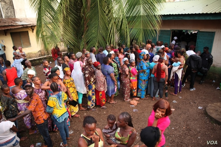 Voters wait to cast their votes outside a polling station in Conakry, Guinea on October 11, 2015. (Photo: C. Stein)