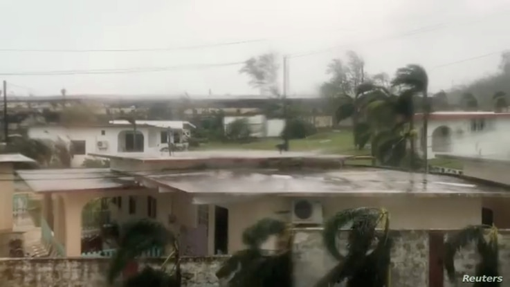 Trees sway during a storm as Super Typhoon Yutu descends upon Saipan, Northern Mariana Islands, Oct. 25, 2018, in this image taken from a video obtained from social media.