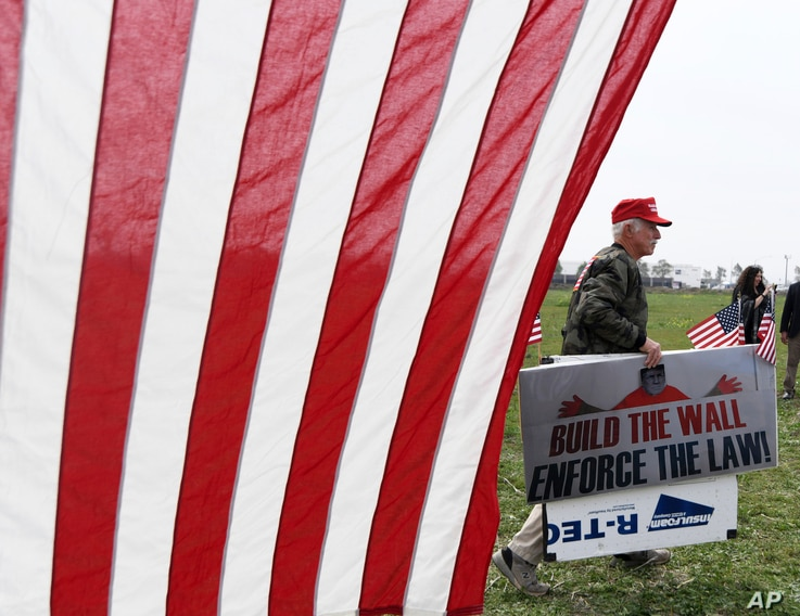 """A supporter of President Donald Trump walks by during a rally for the president's visit, March 13, 2018, in San Diego. Trump on Tuesday inspected prototypes on display in California for his """"big, beautiful border wall."""""""