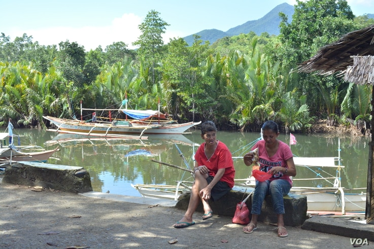 A woman and her neighbor chat while she sorts fish in this small fishing town along Ulugan Bay, which fronts the South China Sea, in  Bahile, Palawan province, Philippines. (Photo: Simone Orendain for VOA)