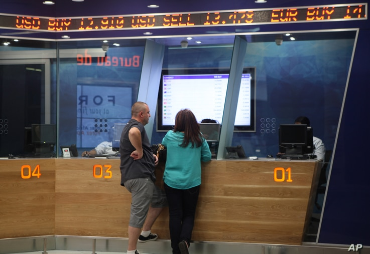 FILE - A man and woman stand below a ticker at the counter of a foreign currency exchange bureau at Johannesburg's OR Tambo International Airport, Aug. 24, 2015.