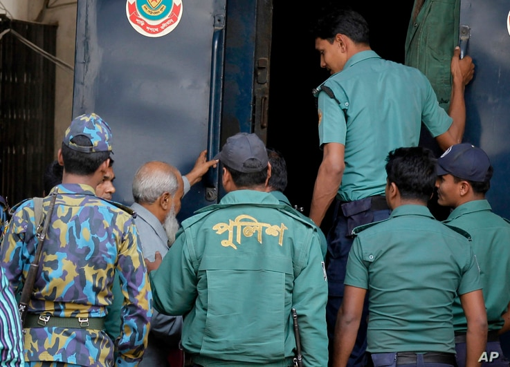 Bangladeshi policemen escort Obaidul Haque Taher, third from left, after he was sentenced to death for his involvement in killing, kidnapping and looting during the country's independence war against Pakistan in 1971, by a Bangladeshi tribunal in Dha...