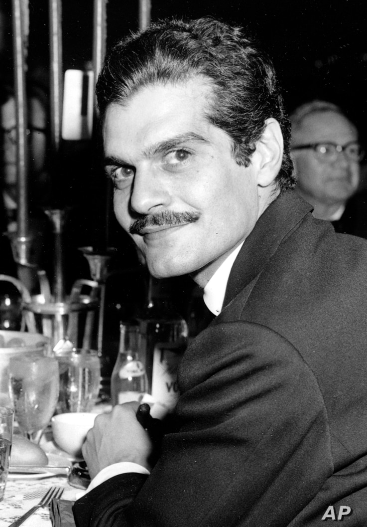 "FILE - In this Dec. 21, 1962 file photo, actor Omar Sharif poses for a photo at a dinner party following the movie premiere of ""Lawrence of Arabia"" in Hollywood, California."
