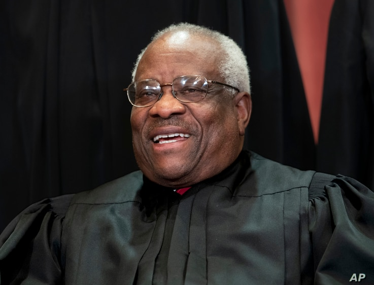 FILE - Associate Justice Clarence Thomas sits with fellow Supreme Court justices for a group portrait at the Supreme Court Building in Washington, Nov. 30, 2018.