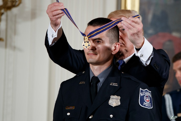 President Donald Trump presents the Medal of Valor to Alexander Jensen of the Alexandria, Virginia Police Department during a ceremony in the East Room of the White House in Washington, July 27, 2017.