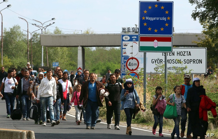 Migrants and refugees cross  the border between Hungary and Austria, near Nickelsdorf, Austria, Sept. 10, 2015.