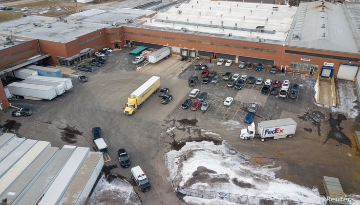 An aerial photo of police and emergency vehicles parked in a lot adjacent to a warehouse at the scene of a mass shooting involving multiply casualties in Aurora, Ill., Feb. 15, 2019.