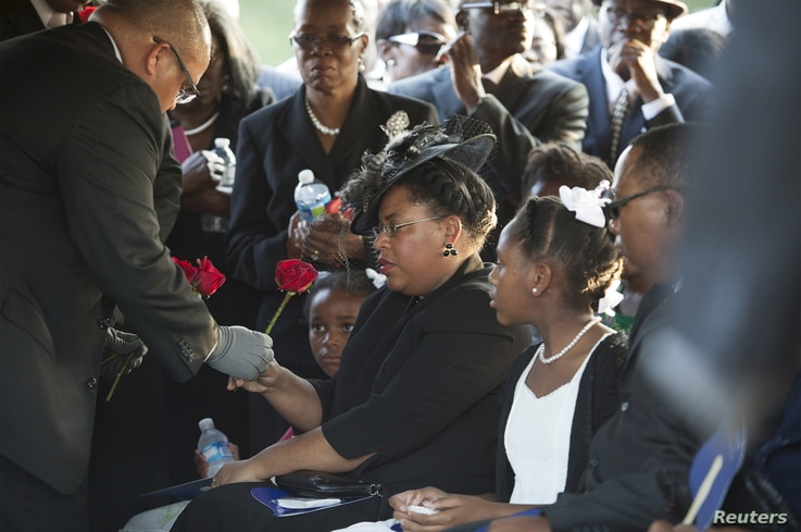 Jennifer Pinckney accepts a rose at the burial of her husband, the Reverend Clementa Pinckney, at the St James AME Church Cemetery in Marion, South Carolina, June 26, 2015.