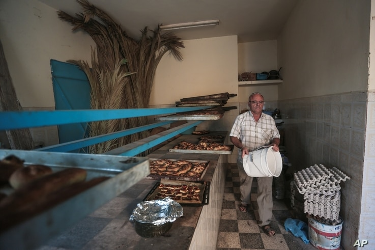 Yofel Sabbagh, 46, walks inside a bakery as he prepares Challah, a special Jewish bread, on the eve of Shabbath, at Hara Kbira, the main Jewish neighborhood on the Island of Djerba, southern Tunisia, Oct. 30, 2015.