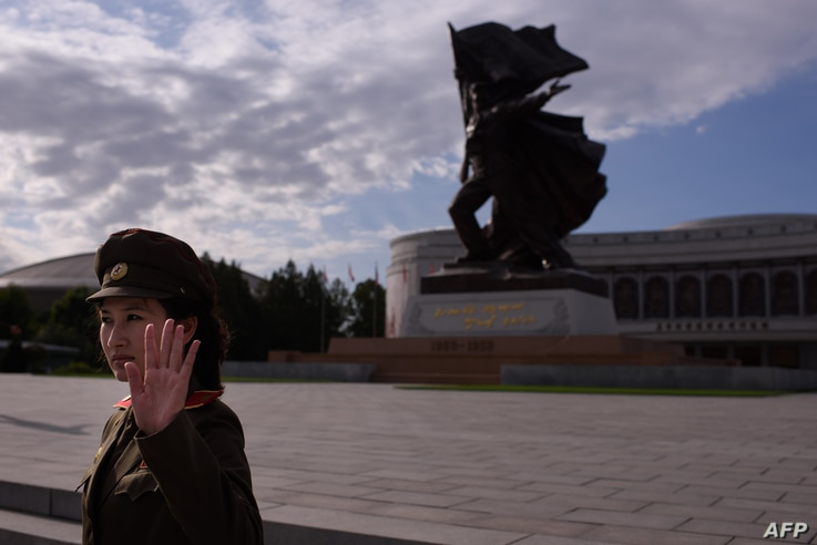 A uniformed tour guide gestures to tourists outside the War Museum in Pyongyang, North Korea, Oct. 9, 2015.