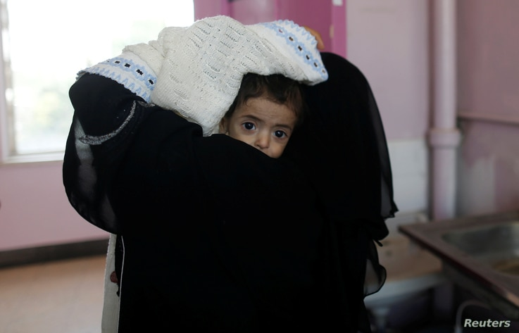 A woman carries a child at the malnutrition ward of al-Sabeen hospital in Sanaa, Yemen Sept.11, 2018.