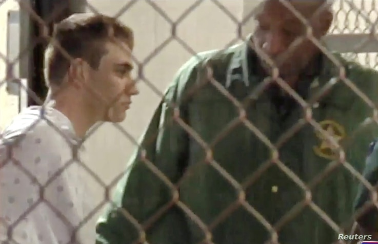 Police escort Nikolas Cruz into Broward County Jail following a shooting incident at Marjory Stoneman Douglas High School, in Fort Lauderdale, Florida, Feb. 15, 2018 in a still image from video.