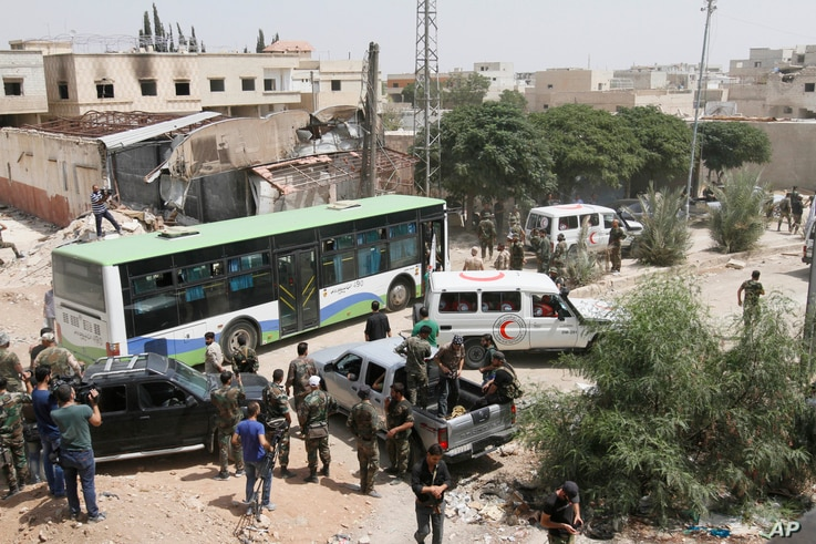 Syrian government buses and a number of the Syrian Arab Red Crescent ambulances at the entrance of Daraya, a suburb of Damascus, Syria, Aug. 26, 2016. Rebels in Daraya agreed to evacuate after four years of grueling bombardment and a crippling siege ...