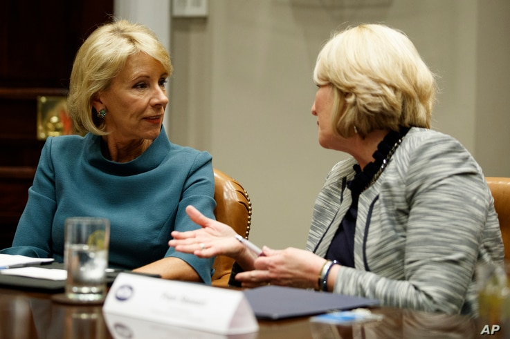 Secretary of Education Betsy DeVos, left, speaks with Commissioner Pam Stewart of the Florida Department of Education before a meeting between President Donald Trump and state and local officials to discuss school safety, in the Roosevelt Room of the...