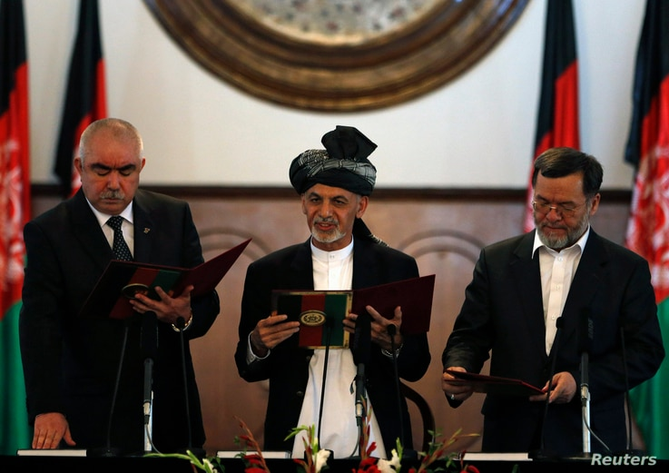 FILE - Afghanistan's President Ashraf Ghani Ahmadzai (C) stands with his first vice president Abdul Rashid Dostum (L) and second vice president Sarwar Danish as they take the oath during his inauguration as president in Kabul, Sept. 29, 2014.
