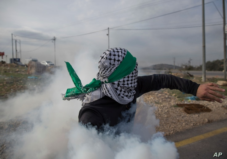A Palestinian protester returns a teargas canister during clashes with Israeli troops following protests against U.S. President Donald Trump's decision to recognize Jerusalem as the capital of Israel, at the outskirts of the West Bank city of Bir Zei...