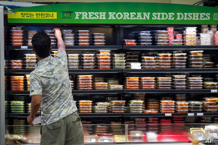 FILE - A man reaches for a food item at the Super H Mart Asian grocery in Fairfax, Virginia, July 20, 2015. Classic Korean food items are showing up with more frequency on American menus and grocery shelves.