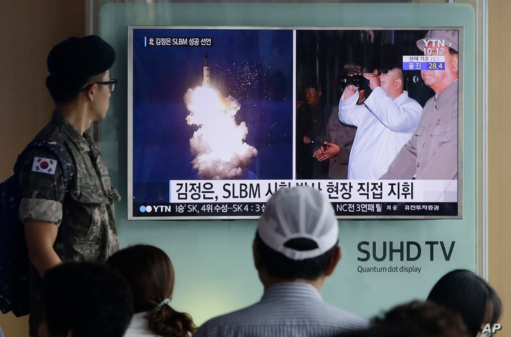A South Korean army soldier watches a TV news program showing images published Thursday in North Korea's Rodong Sinmun newspaper of North Korea's ballistic missile launch and North Korean leader Kim Jong-un, at Seoul Railway station in Seoul, South K