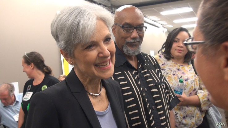 Presumptive Green Party presidential nominee Jill Stein, with her chosen running mate, Ajumu Baraka, in the background, greets supporters at the party's nominating convention in Houston, Aug. 5, 2016. (G. Flakus/VOA)