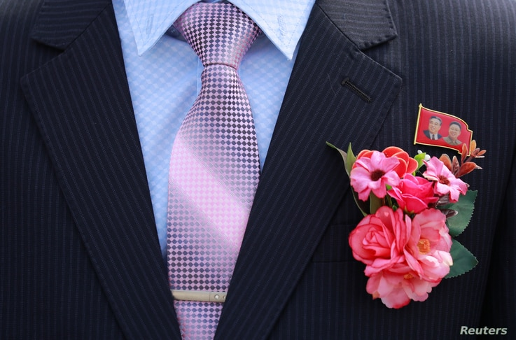 A bridegroom wears a badge with portraits of late North Korean leaders Kim Il Sung and Kim Jong Il in Pyongyang, North Korea, Sept. 11, 2018.