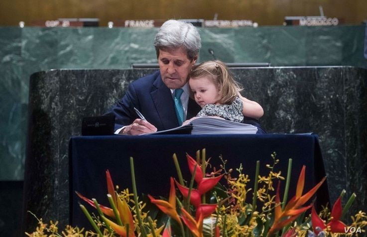 U.S. Secretary of State John Kerry signs the Paris Climate Agreement at UN headquarters with his granddaughter on his lap