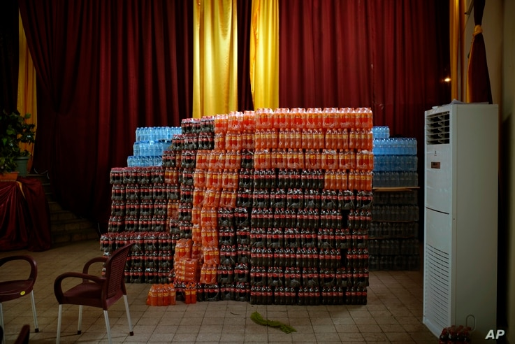 FILE - Crates of soft drinks are stored next to a stage prepared for a victory party for Presidential candidate Emmanuel Ramazani Shadary in the event of his winning the presidential elections in Kinshasa, Congo, Jan. 4, 2019.