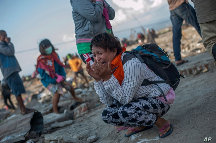 Residents react as rescuers recover the body of a tsunami victim in a village heavily damaged by Friday's tsunami in Palu, Central Sulawesi, Indonesia Indonesia, Oct. 3, 2018.