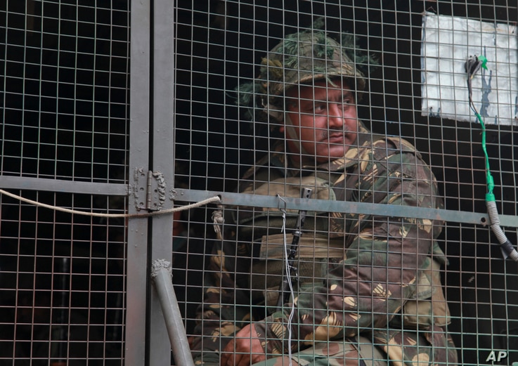 An Indian army soldier looks from inside an army vehicle at the Indian air force base in Pathankot, India, Jan.4, 2016.