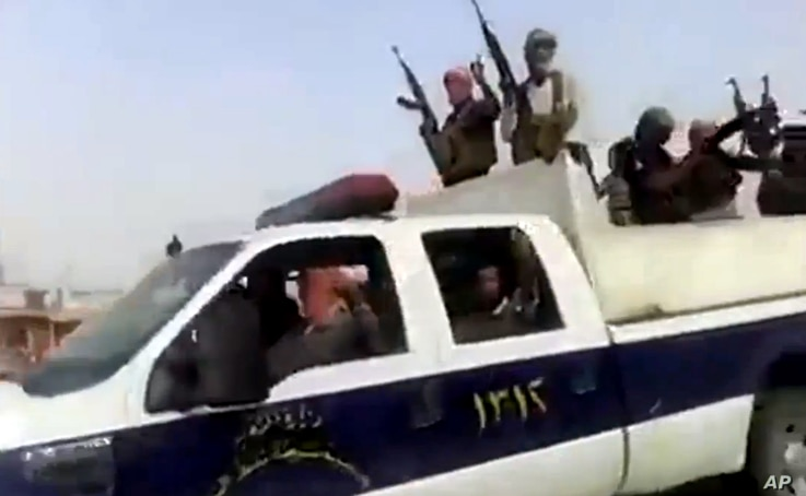 This June 17, 2014 image taken from video uploaded to a militant social media account shows Islamic State of Iraq and the Levant militants arriving at the oil refinery in Beiji, Iraq.